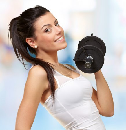 Photo for Portrait of a young pretty woman holding weights and doing fitness indoor - Royalty Free Image