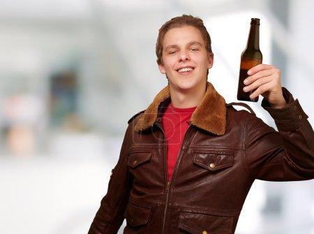 Portrait of young man holding beer indoor