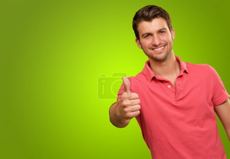 Photo for Young man smiling with thumbs up isolated on green background - Royalty Free Image