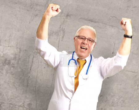 Senior Male Doctor In A Winning Gesture