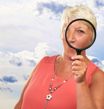 Senior Woman Looking Through A Magnifying Glass