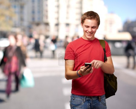 Photo for Portrait of young man touching mobile screen at crowded street - Royalty Free Image