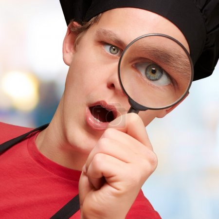 Portrait of young cook man looking through a magnifying glass in