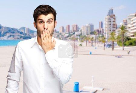 Photo pour Portrait de jeune homme surpris contre une plage - image libre de droit