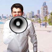 Portrét mladého muže, překypující megafon proti pláži