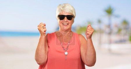 Photo pour Portrait d'une femme âgée avec un poing fermé, Extérieur - image libre de droit