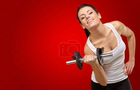 Young woman holding dumbells