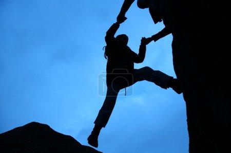 Photo pour Silhouette d'escalade, obtient un coup de main pour se lever - image libre de droit
