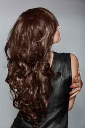 Photo for Back of the woman with long brown curly hair with healthy shine, wearing a leather dress over a studio background. - Royalty Free Image