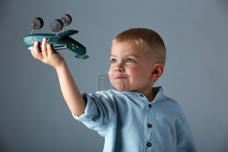 Young boy with wooden airplane