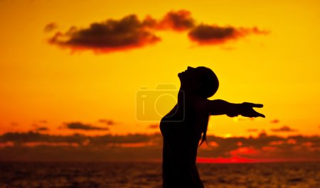Woman silhouette over sunset