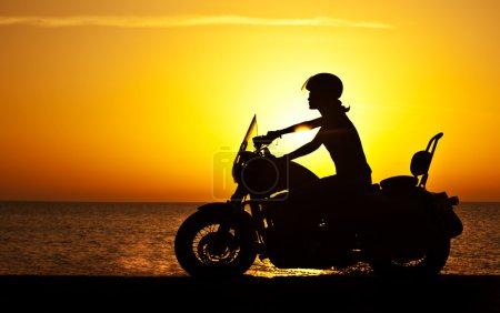 Photo pour Femme motard sur le coucher du soleil, moto d'équitation féminine, conducteur de moto voyageant, fille course sur la route de la plage, mode de vie de liberté - image libre de droit
