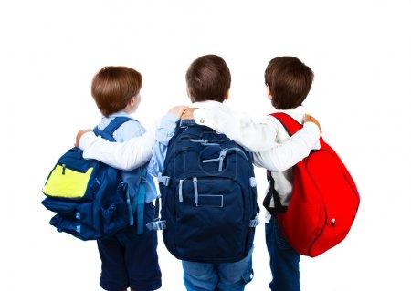 Photo pour Trois écoliers isolés sur fond blanc, vue arrière de trois adolescents avec des sacs à dos colorés, meilleurs amis debout et câlins en studio, retour à l'école, concept éducatif - image libre de droit