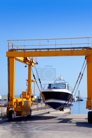 Crane travelift lifting a boat on blue sky day