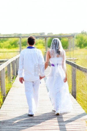 Photo for Couple happy in wedding day walking in outdoor rear view - Royalty Free Image