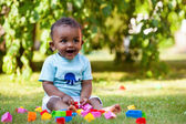 Little african american baby boy playing in the grass