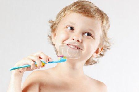 Photo pour Jeune garçon se brossant les dents sur un fond blanc - image libre de droit