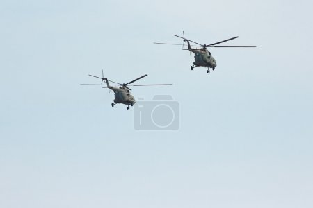Two russian military transport helicopter MI-8 in cloudy sky