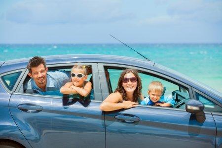Photo pour Une famille de quatre, mère, père, fils et fille volant d'une voiture sur une journée ensoleillée dans emplacement chaud, mer backround - image libre de droit