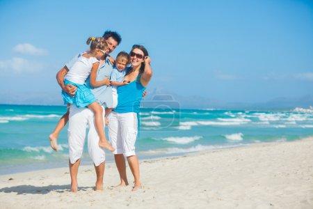 Photo pour Famille de quatre personnes s'amuser sur la plage tropicale - image libre de droit