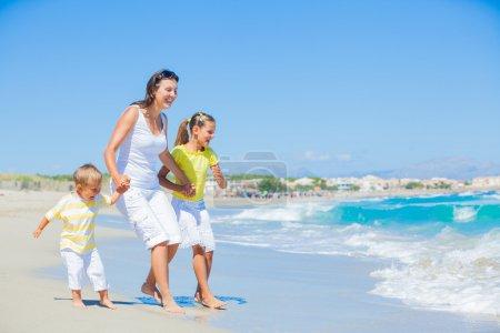 Photo pour Famille heureuse de trois - mère et son enfant en cours d'exécution et de s'amuser sur la plage tropicale - image libre de droit