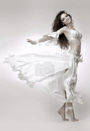 Beautiful young belly dancer wearing white dress