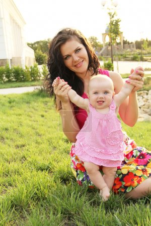 Photo for Happy Baby making first steps with mother help - Royalty Free Image