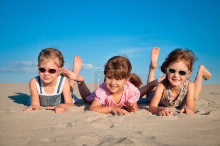 Adorable three little girl playing on the sandy beach