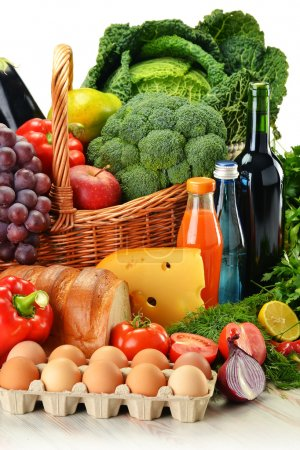 Photo for Groceries in wicker basket including vegetables, fruits, bakery and dairy products and wine isolated on white - Royalty Free Image