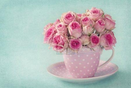 Photo pour Roses roses dans une tasse sur fond bleu - image libre de droit