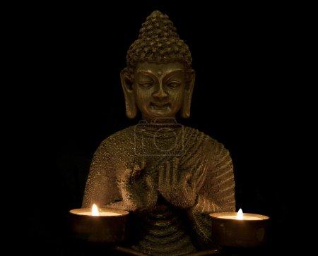 Foto de Budha con dos velas sobre un fondo negro - Imagen libre de derechos