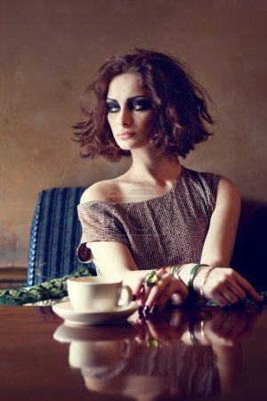 Beautiful brunette woman sitting alone in a restaurant