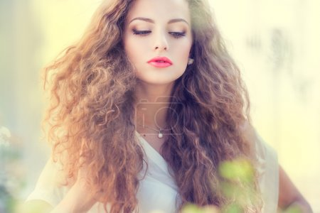 Foto de Hermosa joven con el pelo rizado hermoso al aire libre - Imagen libre de derechos