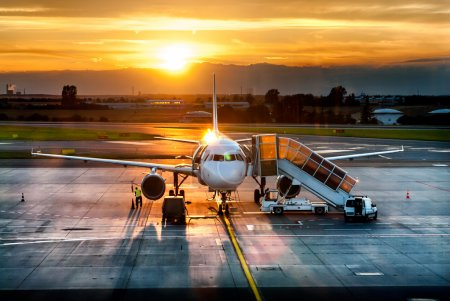 Photo for Airplane near the terminal in an airport at the sunset - Royalty Free Image