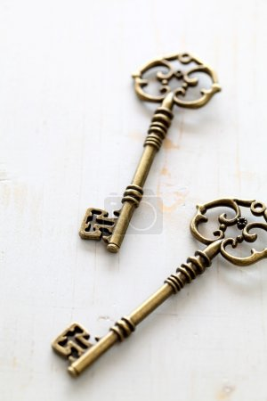 Photo for Antique keys isolated on wooden table - Royalty Free Image