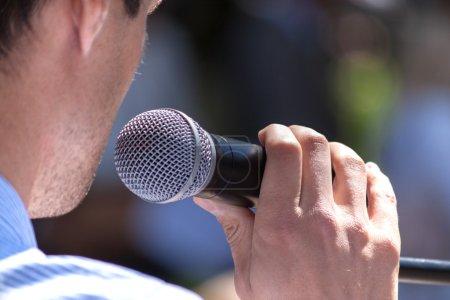 Photo pour Haut-parleur tient le microphone près - image libre de droit