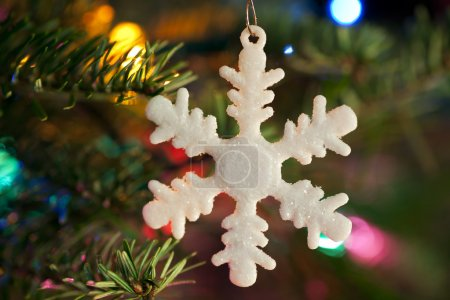 Photo for White snow flake Christmas ornament hanging on Christmas tree with out of focus lights. - Royalty Free Image