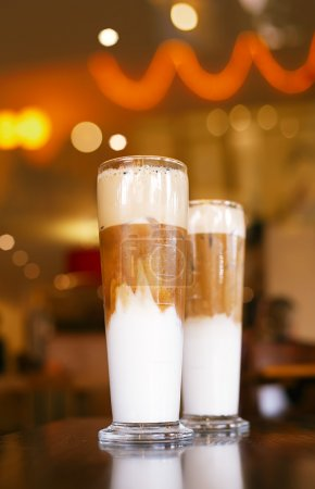 Iced coffee latte with lights on background in a tall glasses