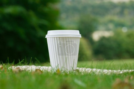 Photo for A white coffee cup in the grass, shallow DOF - Royalty Free Image