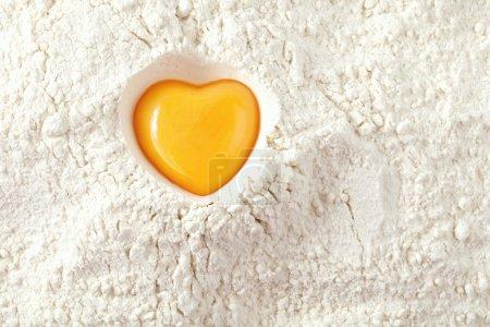 Love to bake it! egg yolk on flour, full frame...