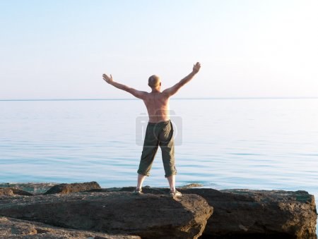 Man with lifted hands on the sea coast
