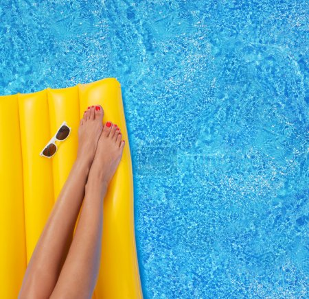 Photo for Woman relaxing in a pool - feet close up - Royalty Free Image
