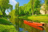 Spring landscape with boat on the river. Pułtusk, Poland.
