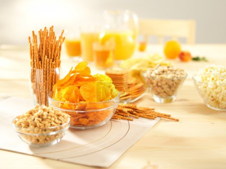 Photo for A lots of salty snacks with juice on a wooden table - Royalty Free Image