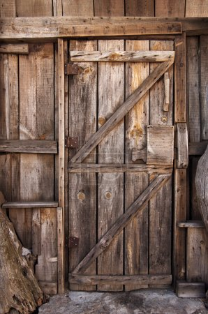 Photo for Detail of a closed wooden door with big wooden lock in an old shack - Royalty Free Image