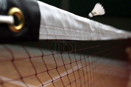 Photo pour Photo de la navette badminton net de près et d'une navette rapide au-dessus du filet dans un terrain de badminton intérieur - image libre de droit