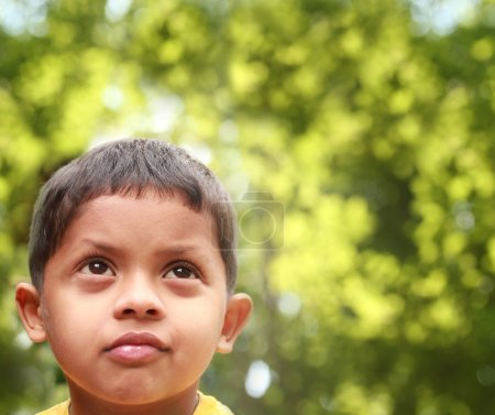 Young indian boy of kinder-garten school age thinking or dreamin
