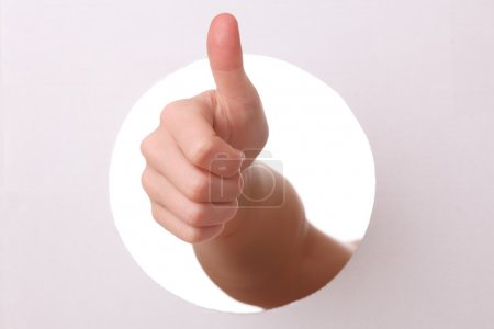 Photo for Arm reaches trough a hole with thumbs up - Royalty Free Image