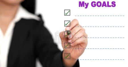 Asian business woman writing goal list on white bo...