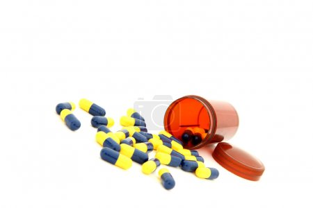 Photo for Perspective of isolated capsules spilling out from small bottle - Royalty Free Image
